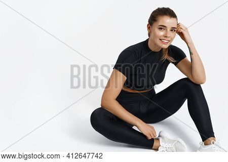 Fit And Healthy Female Athlete Sitting On Floor In Sport Clothing. Muscular Fitness Woman Resting Af