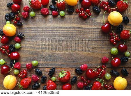 Berry And Fruit Background. Frame Of Fresh And Juicy Berries On Wooden Background. Copy Space For Te