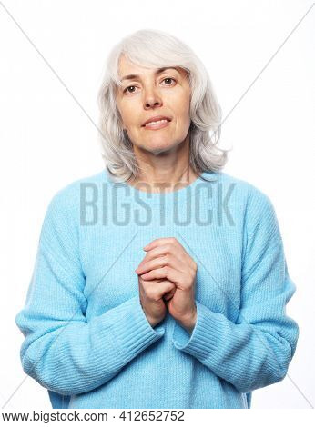 Senior grey-haired woman wearing blue sweater standing over isolated white background praying with hands together asking for forgiveness smiling confident.