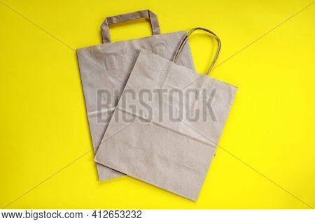 Recycled Brown Paper Shopping Bag With Handle, Isolated On Yellow Background, Flat Lay, Mockup. Two