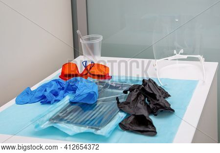 Sterile Medical Instruments In Packaging And Blue And Black Disposable Gloves In A Medical Office. S