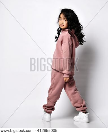 Back View Of A Korean Child Girl In A Warm Dusty Pink Jumpsuit With A Hood, She Looks Back And Looks
