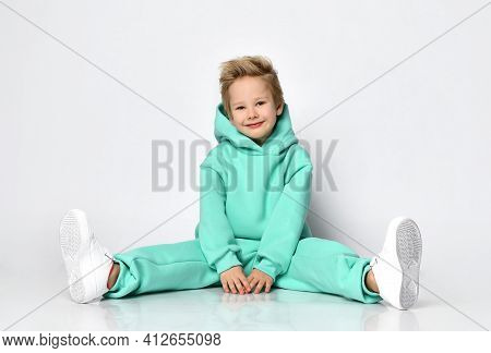 Playful Boy In A Warm Tracksuit And Sneakers Sits Against A Gray Wall. A Child In A Turquoise Fleece