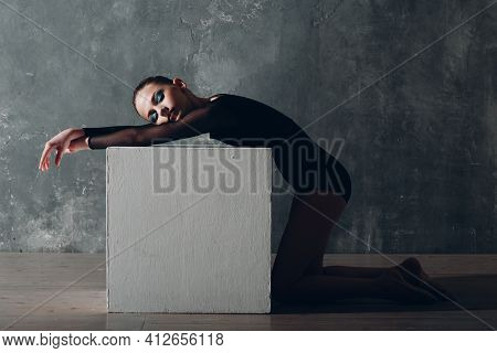 Young Girl Professional Gymnast Woman Rhythmic Gymnastics Relaxing With White Cube At Studio
