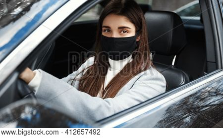 Covid-19. Elegant Businesswoman Driving To Work In Face Mask. Female Driver Sitting In Car, Looking