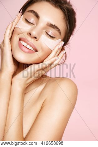 Beauty Face. Smiling Woman Using Under Eye Patches To Nourish And Moisturize Gentle Skin, Reduce Puf