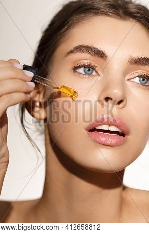 Beauty And Daily Care Concept. Young Woman Using Rose Damask Essential C-serum For Better Facial Ton