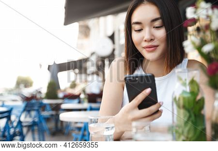 Close-up Of Modern Asian Woman Sitting At Sidewalk Cafe With Mobile Phone. Girl Reading Text Message