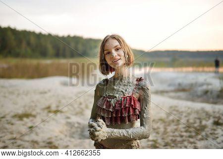 Young Girl Taking Healing Mud Baths On Lake Gela Near Vilnius, Lithuania. Child Having Fun With Mud.