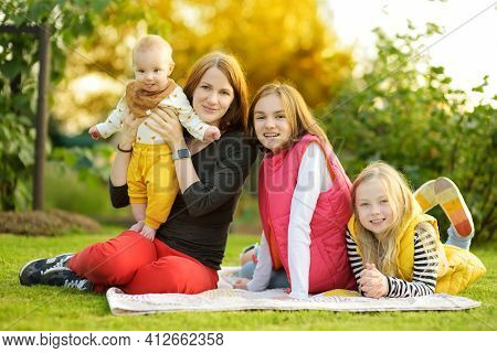 Mother And Three Children Having Fun On Autumn Day In City Park. Adorable Baby Boy Being Held By His