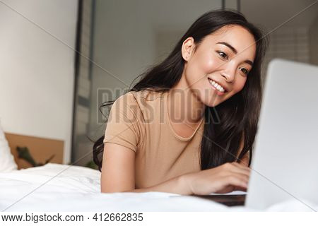 Portrait Of Beautiful Happy Asian Woman Lying In Bed Relaxed And Looking At Laptop Screen. Girl Smil