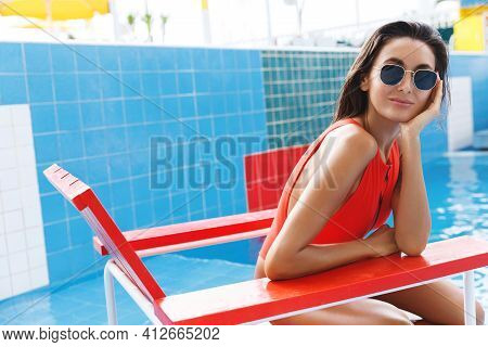Tourism And Vacation Concept. Beautiful Brunette Woman In Baywatch Red Swimming Suit, Sitting On Lif