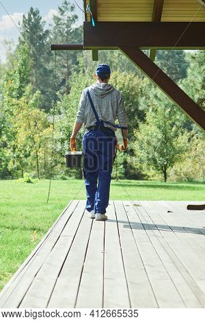 Full Length Shot Of Young Workman In Blue Overalls Carrying Toolbox After Doing Repair Work In The C