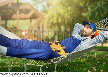 Relaxed Young Male Builder Wearing Blue Overalls And Cap Taking A Break, Lying In A Hammock Outdoors