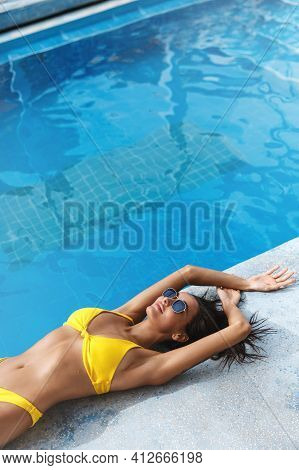 Side View Of Sexy Tanned Woman In Yellow Bikini And Sunglasses Lying Down Summer Day Near Poolside.