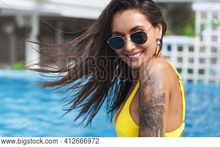 Close-up Of Beautiful Tanned Woman With Tattoo In Yellow Bikini, Smiling Camera Near Swimming Pool.