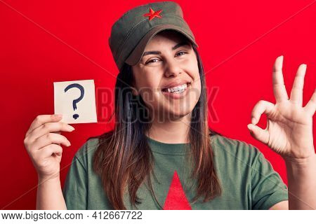 Beautiful woman wearing cap with red star communist symbol holding question mark reminder doing ok sign with fingers, smiling friendly gesturing excellent symbol