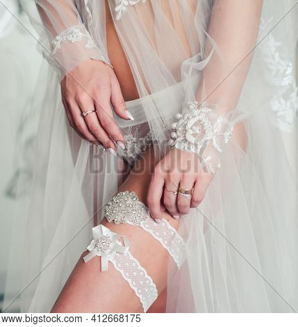 Tender Morning Of The Bride. The Bride In A White Negligee Wears A Garter On Her Leg. Morning Weddin