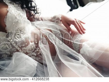 Tender Morning Of The Bride. The Bride Out Of Focus In A White Negligee Wears A Garter On Her Leg. M