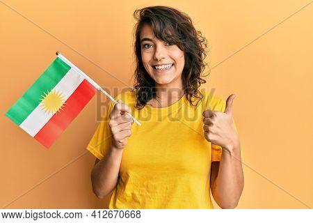 Young hispanic woman holding san fernando flag smiling happy and positive, thumb up doing excellent and approval sign