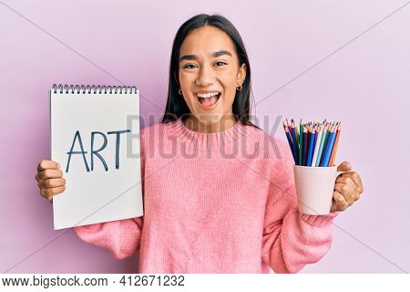 Young asian woman holding art notebook and colored pencils smiling and laughing hard out loud because funny crazy joke.