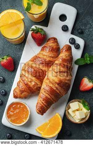 Fresh Sweet Croissants With Butter And Orange Jam For Breakfast. Continental Breakfast On A Dark Con