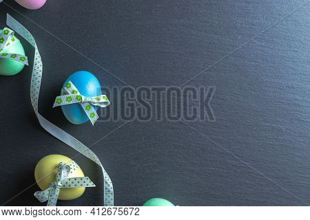 Easter Background Blue. Colourful Egg With Tape Ribbon On Dark Rough Stone Background In Happy Easte