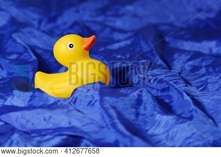 yellow rubber ducky on blue cloth