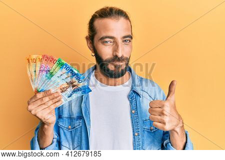 Attractive man with long hair and beard holding swiss franc banknotes smiling happy and positive, thumb up doing excellent and approval sign