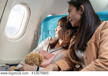 Asian Mother And Daughter Sitting On Board In Airplane, Looking Outside Window Together. The Girl Ho