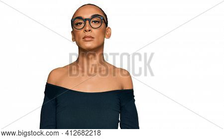 Hispanic transgender man wearing make up and long hair wearing women clothes relaxed with serious expression on face. simple and natural looking at the camera.