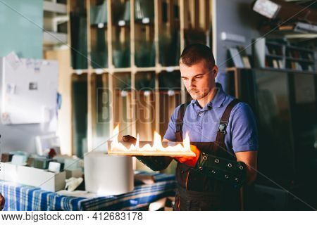 Glazier worker cutting glass with fire in a workshop. Industry