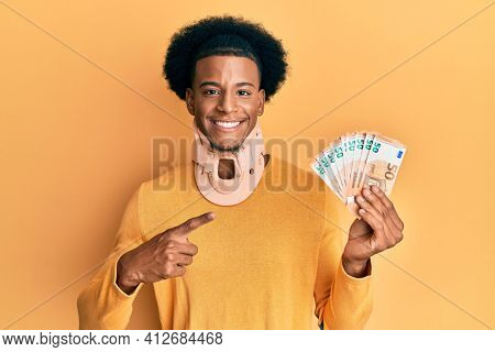African american man with afro hair wearing cervical neck collar and holding money from insurance smiling happy pointing with hand and finger