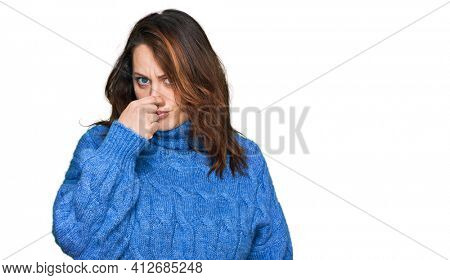 Young plus size woman wearing casual clothes smelling something stinky and disgusting, intolerable smell, holding breath with fingers on nose. bad smell