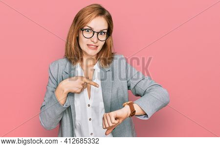 Young caucasian woman wearing business style and glasses in hurry pointing to watch time, impatience, upset and angry for deadline delay