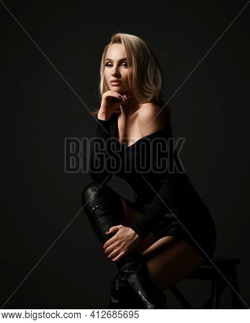 Sexy Blonde Woman In Black Clothes With Naked Shoulder And High Leather Boots Is Sitting On Stool Lo