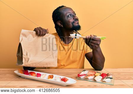 Handsome young black man eating take away sushi sitting on the table smiling looking to the side and staring away thinking.