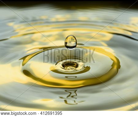 Water Drops Frozen At High Speed In Golden Pool Of Water Showing Surface Tension And Droplet Structu
