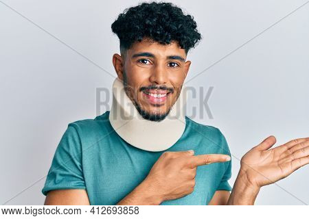 Young arab handsome man wearing cervical neck collar amazed and smiling to the camera while presenting with hand and pointing with finger.