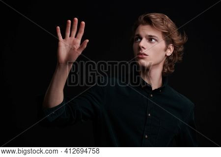 Portrait of a handsome young man with wavy blond hair posing on a black background. Men's beauty. Copy space.