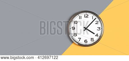 Plain Wall Clock In The Center On Grey And Orange Banner