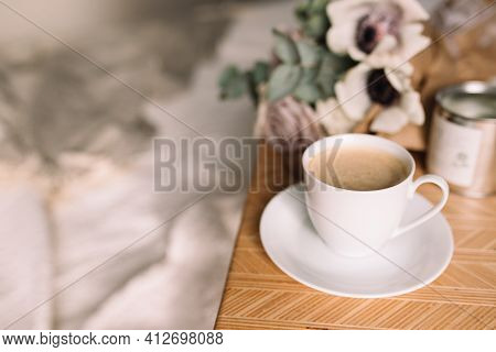 Romantic Morning. Wooden Coffee Table With Flowers On Bed With Plaid, Coffee Cup, Flowers And Candle