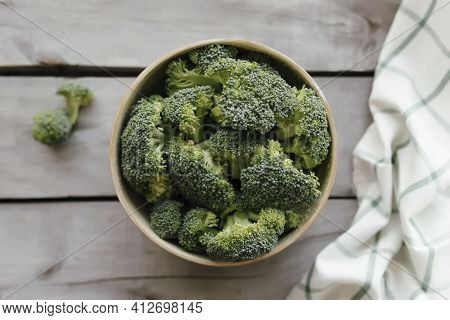 Green Fresh Broccoli In Bowl On Wooden Background, White Towel. Healthy Eating Concept. High Quality