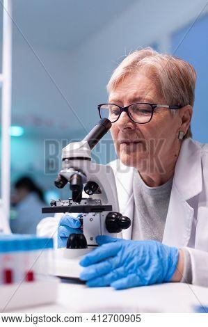 Senior Scientist Chemist Analysing Reaction Of Virus On Microscope In Laboratory. Woman Working On S