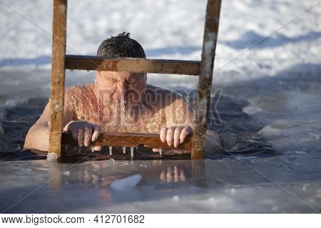 A Man Plunges Into An Ice-hole During The Winter Festival Of The Baptism Of Jesus. A Man Swims In Th
