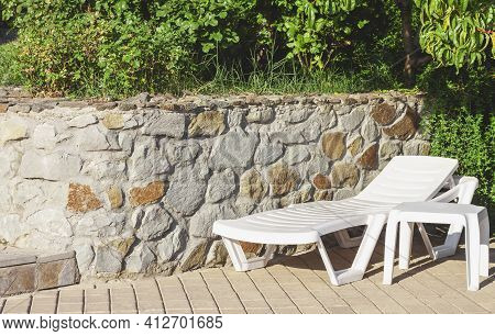 White Plastic Chaise Lounge And Table On A Tiled Surface Next To A Stone Wall Under Green Trees On A