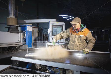 A Furniture Manufacturing Worker At A Cutting Machine Makes Furniture Parts. Furniture Manufacturing