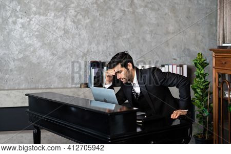 Tired And Worried Businessman At Workplace In Office Holding His Head On Hands After Late Night Work