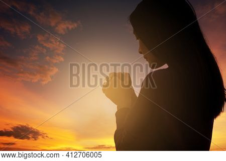 Christian Woman Praying Worship At Sunset. Hands Folded In Prayer. Worship God With Christian Concep