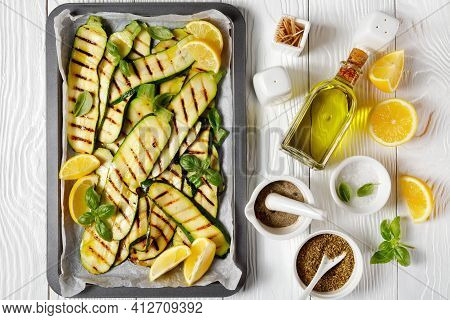 Grilled Zucchini Slices On A Sheet Pan With Lemon, Olive Oil, Spices And Fresh Basil Leaves On A Whi